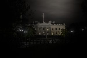 The White House at night, eerily lit, the ghosts are prowling within