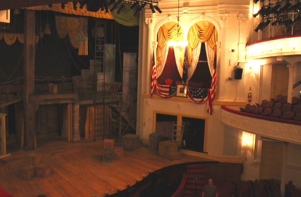 The stage of Ford's Theatre, where dramatic light illuminates the Presidents box, where Lincoln haunts the stage