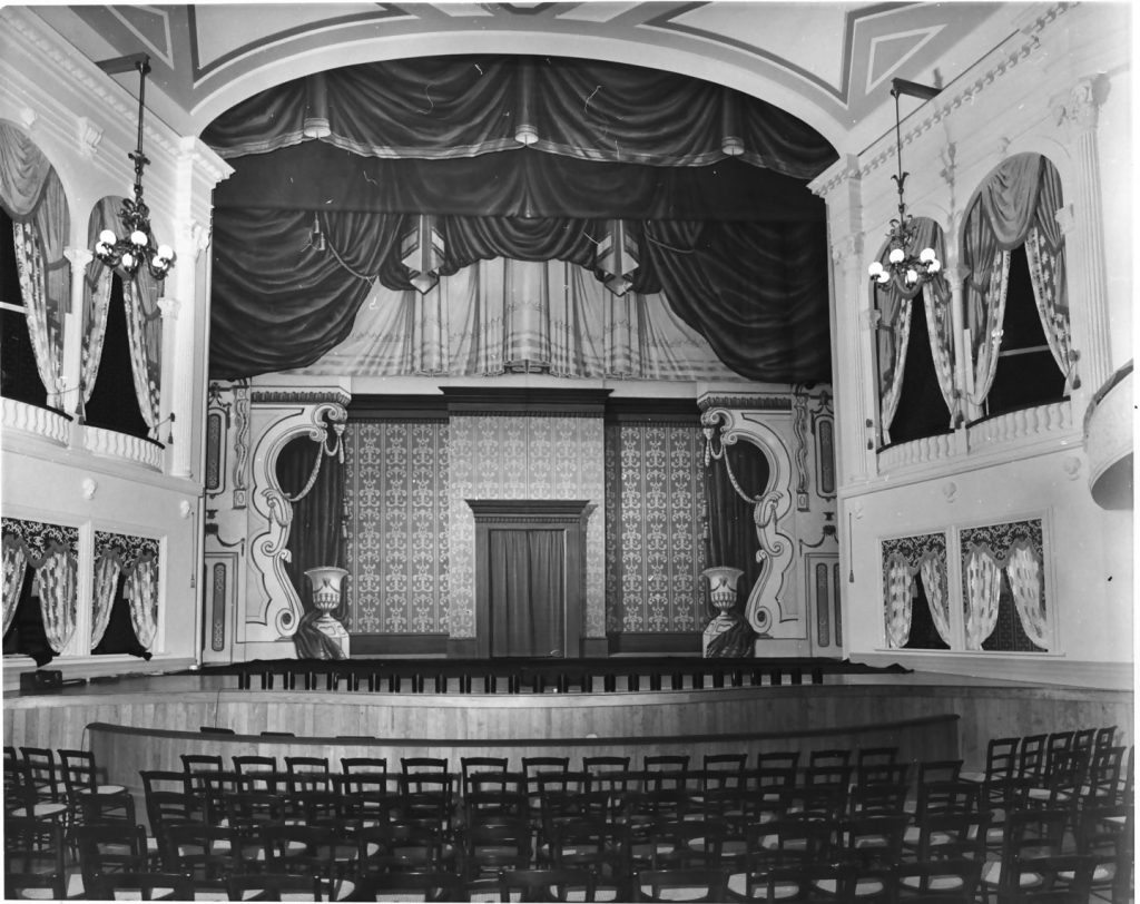 A black and white photo of the stage of Ford's Theatre, where President Abraham Lincoln was shot, and his ghost still haunts.