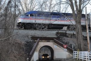 A train passing over a tunnel with a car driving through it